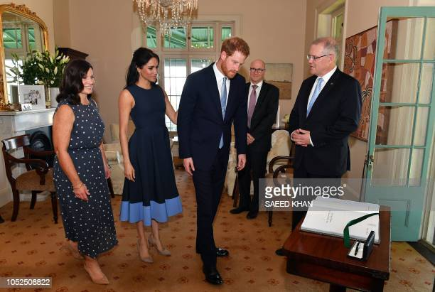 Britain's Prince Harry and his wife Meghan Duchess of Sussex proceed to sign a visitors book prior to their meeting with Australias Prime Minister...