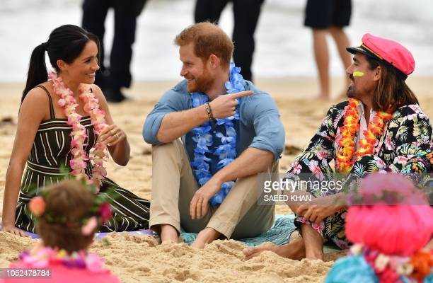 Britain's Prince Harry and his wife Meghan Duchess of Sussex share smile as they attend a Fluro Friday session run by OneWave a local surfing...