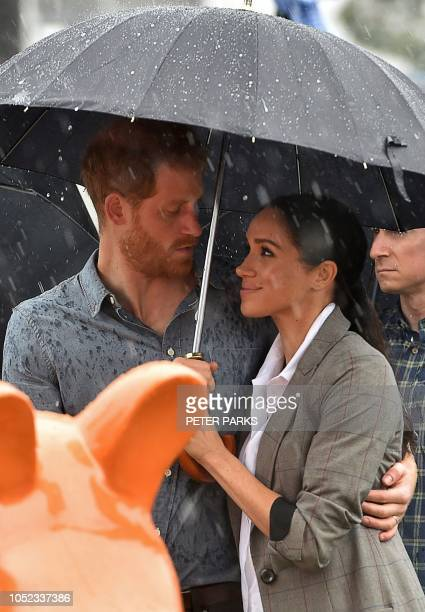 Britain's Prince Harry and his wife Meghan, Duchess of Sussex watch aboriginal dances at Victoria Park in Dubbo on October 17, 2018. - Prince Harry...