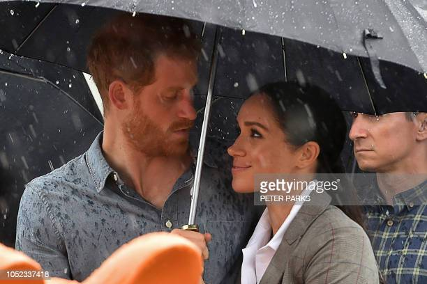 TOPSHOT Britain's Prince Harry and his wife Meghan Duchess of Sussex watch aboriginal dances at Victoria Park in Dubbo on October 17 2018 Prince...