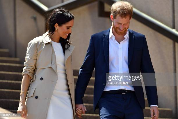 Britain's Prince Harry and his wife Meghan smile as they walk down the stairs of Sydneys iconic Opera House to meet people in Sydney on October 16...