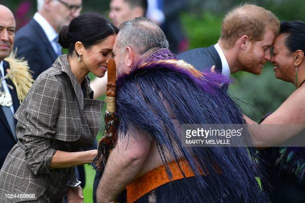 Britain's Prince Harry and his wife Meghan the Duchess of Sussex receive a hongi or traditional Maori greeting from elders during an official...