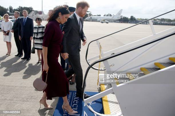 Britain's Prince Harry and his wife Meghan the Duchess of Sussex board a plane for New Zealand from Sydney airport on October 28 2018 Prince Harry...