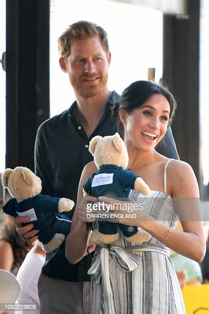 Britain's Prince Harry and his wife Meghan, the Duchess of Sussex hold stuffed toys during a meet-the-people walk at Kingfisher Bay Resort on Fraser...