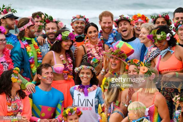 TOPSHOT Britain's Prince Harry and his wife Meghan the Duchess of Sussex pose during a 'Fluro Friday' session run by OneWave a local surfing...