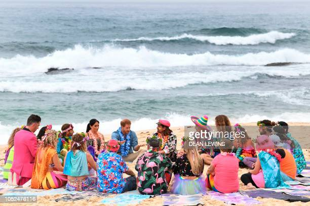 Britain's Prince Harry and his wife Meghan the Duchess of Sussex take part in a Fluro Friday session run by OneWave a local surfing community group...
