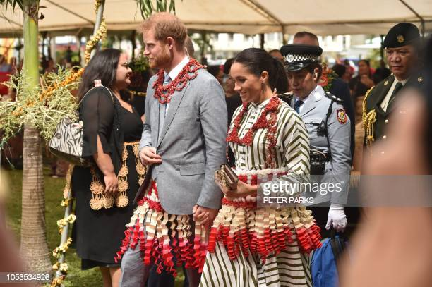 Britain's Prince Harry and his wife Meghan, the Duchess of Sussex visit a craft fair in Nuku'alo in Tonga on October 26, 2018. - Prince Harry and his...