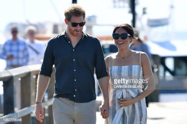 TOPSHOT Britain's Prince Harry and his wife Meghan the Duchess of Sussex walk to attend a meetthepeople session at Kingfisher Bay Resort on Fraser...