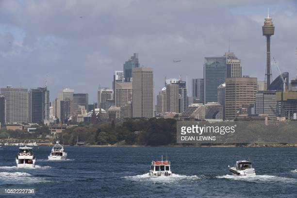 Britain's Prince Harry and his wife Meghan travel by launch on Sydney Harbour following a visit to Taronga Zoo in Sydney on October 16 2018 Prince...