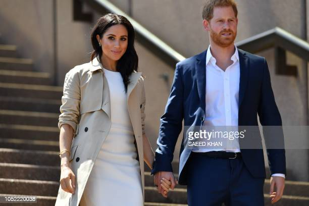 TOPSHOT Britain's Prince Harry and his wife Meghan walk down the stairs of Sydneys iconic Opera House to meet people in Sydney on October 16 2018...