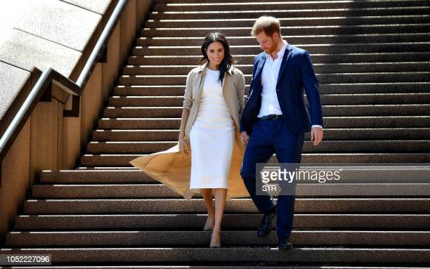 TOPSHOT Britain's Prince Harry and his wife Meghan walk down the stairs of the iconic Opera House to meet people on October 16 2018 Prince Harry and...