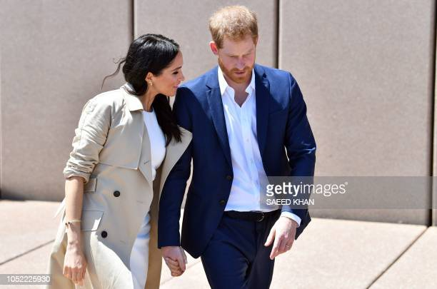 Britain's Prince Harry and his wife Meghan walk outside the Sydneys iconic Opera House on October 16 2018 Prince Harry and Meghan have made their...