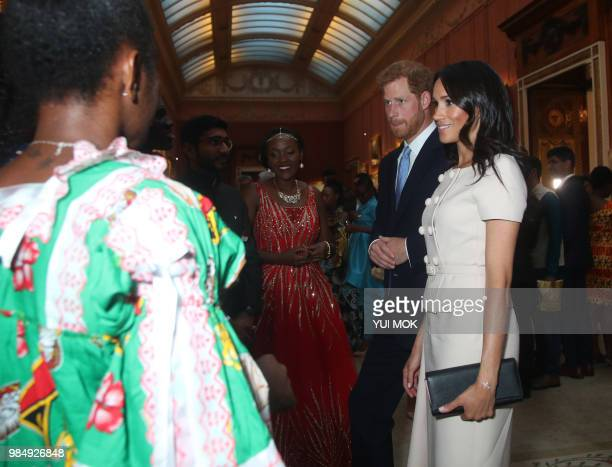 Britain's Prince Harry and Meghan Duke and Duchess of Sussex meet a group of Queen's Young Leaders at a Buckingham Palace reception following the...