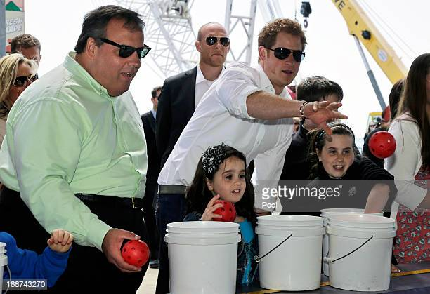 Britain's Prince Harry and New Jersey Gov Chris Christie toss balls for Taylor Cirigliano and sister Allie Cirigliano at a Ball Toss game on the...