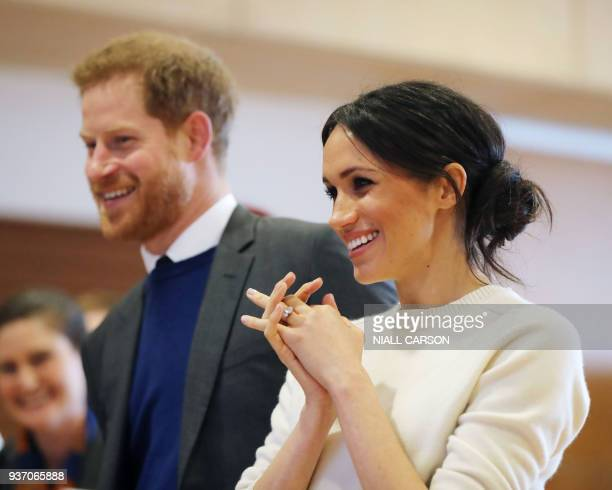 Britain's Prince Harry and Prince Harry's fiancee US actress Meghan Markle speak with staff during a visit to Northern Irelands next generation...