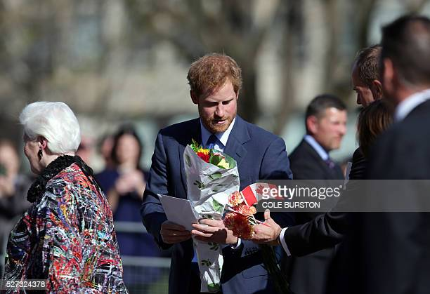 Britain's Prince Harry collects his gifts as he greets admirers outside of Queens Park in Toronto Canada on May 2 2016 after spending the day in the...