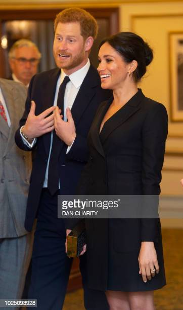 Britain's Prince Harry Duke of Sussex and Britain's Meghan Duchess of Sussex talk with other guests as they arrive to attend a gala performance of...