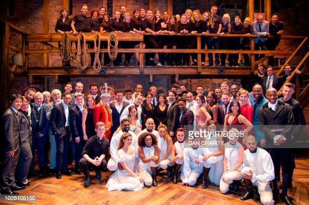 Britain's Prince Harry, Duke of Sussex, and Britain's Meghan, Duchess of Sussex pose with the cast and crew backstage after a gala performance of the...