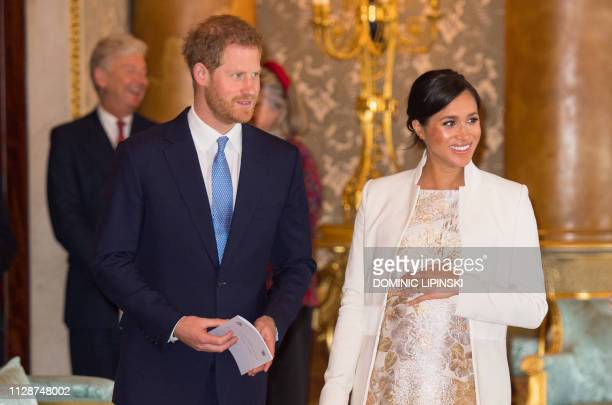 Britain's Prince Harry, Duke of Sussex, and Britain's Meghan, Duchess of Sussex attend a reception to mark the 50th Anniversary of the investiture of...