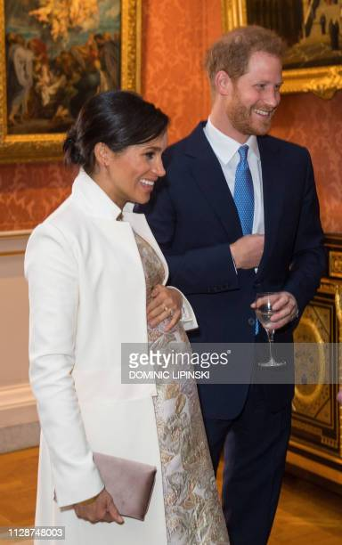 Britain's Prince Harry Duke of Sussex and Britain's Meghan Duchess of Sussex attend a reception to mark the 50th Anniversary of the investiture of...