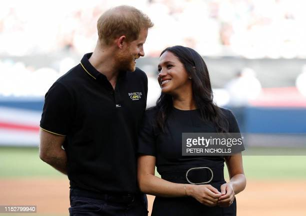 Britain's Prince Harry Duke of Sussex and Britain's Meghan Duchess of Sussex arrive on the field prior to the start of the first of a twogame series...