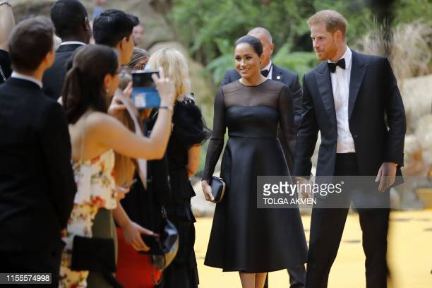 Britain's Prince Harry, Duke of Sussex and Britain's Meghan, Duchess of Sussex pose for a photograph as they arrive for the European premiere of the...