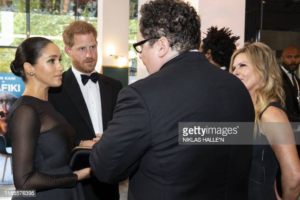 Britain's Prince Harry, Duke of Sussex and Britain's Meghan, Duchess of Sussex chat with US film director Jon Favreau as they arrive to attend the...