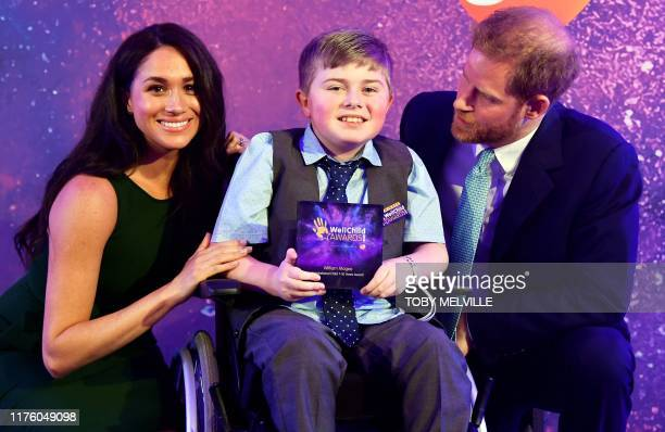 Britain's Prince Harry, Duke of Sussex, and Britain's Meghan, Duchess of Sussex pose for a photograph with award winner William Magee during the...