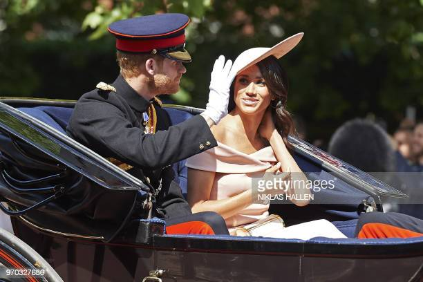 TOPSHOT Britain's Prince Harry Duke of Sussex and Britain's Meghan Duchess of Sussex travel in a horsedrawn carriage down The Mall to Horseguards...
