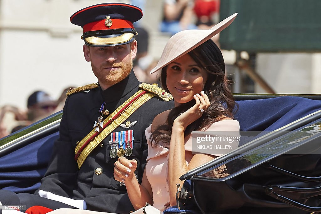 TOPSHOT - Britain's Prince Harry, Duke of Sussex and Britain's Meghan, Duchess of Sussex return in a horse-drawn carriage after attending the Queen's Birthday Parade, 'Trooping the Colour' on Horseguards parade in London on June 9, 2018. - The ceremony of Trooping the Colour is believed to have first been performed during the reign of King Charles II. In 1748, it was decided that the parade would be used to mark the official birthday of the Sovereign. More than 600 guardsmen and cavalry make up the parade, a celebration of the Sovereign's official birthday, although the Queen's actual birthday is on 21 April.