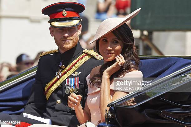 TOPSHOT Britain's Prince Harry Duke of Sussex and Britain's Meghan Duchess of Sussex return in a horsedrawn carriage after attending the Queen's...