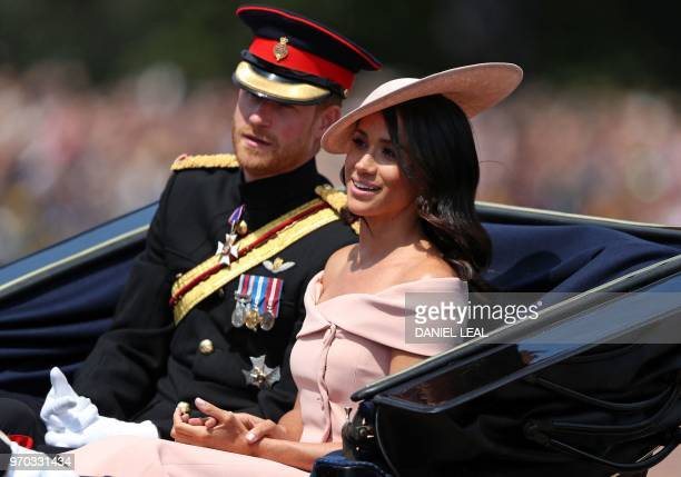 Britain's Prince Harry Duke of Sussex and Britain's Meghan Duchess of Sussex return in a horsedrawn carriage after attending the Queen's Birthday...