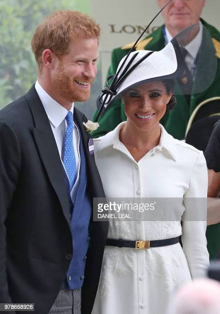 Britain's Prince Harry, Duke of Sussex, and Britain's Meghan, Duchess of Sussex react after presenting the trophy for the St James's Palace Stakes...