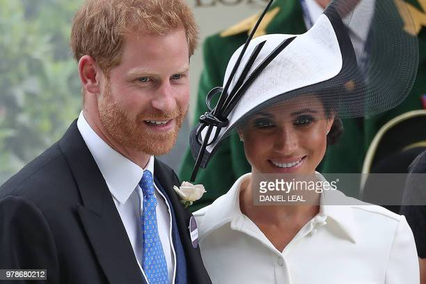 Britain's Prince Harry Duke of Sussex and Britain's Meghan Duchess of Sussex react after presenting the trophy for the St James's Palace Stakes race...