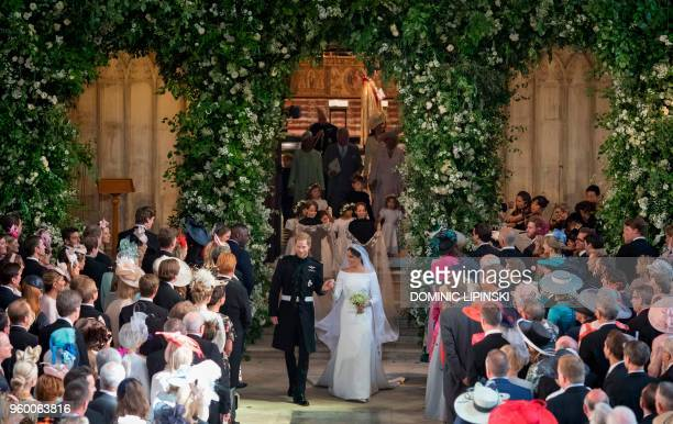 TOPSHOT Britain's Prince Harry Duke of Sussex and Britain's Meghan Markle Duchess of Sussex walk away from the High Altar at the end of their wedding...