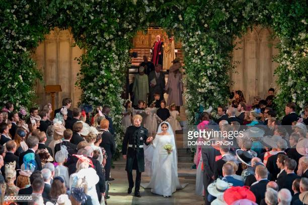 Britain's Prince Harry, Duke of Sussex and Britain's Meghan Markle, Duchess of Sussex, walk back down the aisle away from the High Altar as they...