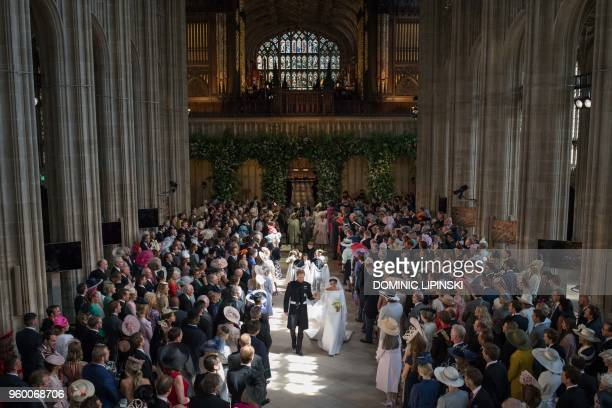 Britain's Prince Harry Duke of Sussex and Britain's Meghan Markle Duchess of Sussex walk back down the aisle away from the High Altar as they leave...