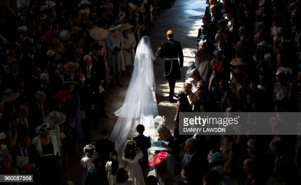 TOPSHOT Britain's Prince Harry Duke of Sussex and Britain's Meghan Markle Duchess of Sussex walk away from the High Altar toward the West Door at the...
