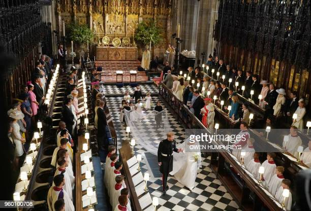 Britain's Prince Harry, Duke of Sussex and Britain's Meghan Markle, Duchess of Sussex, walk away from the High Altar toward the West Door to exit at...