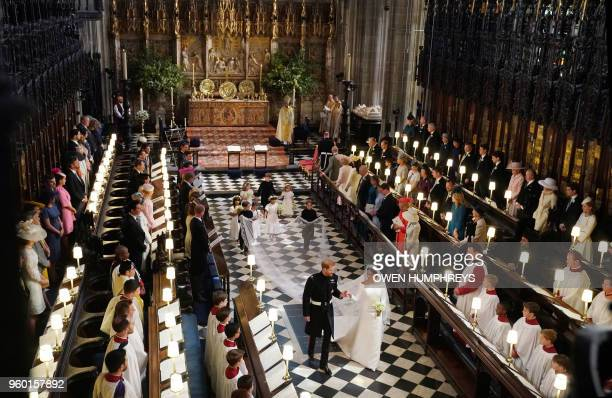 Britain's Prince Harry Duke of Sussex and Britain's Meghan Markle Duchess of Sussex walk away from the High Altar toward the West Door to exit at the...