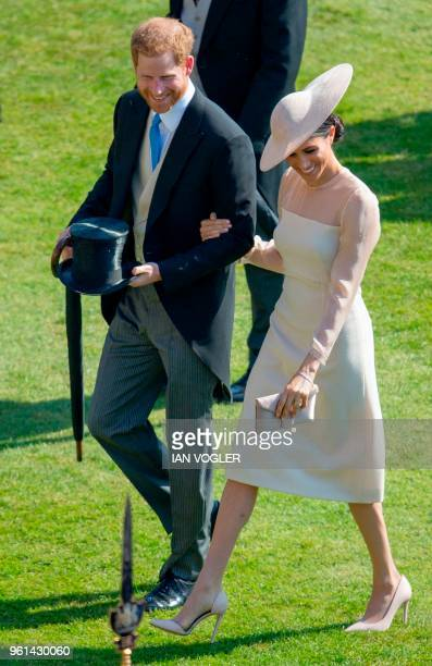 Britain's Prince Harry, Duke of Sussex and his new wife Britain's Meghan, Duchess of Sussex, attend the Prince of Wales's 70th Birthday Garden Party...