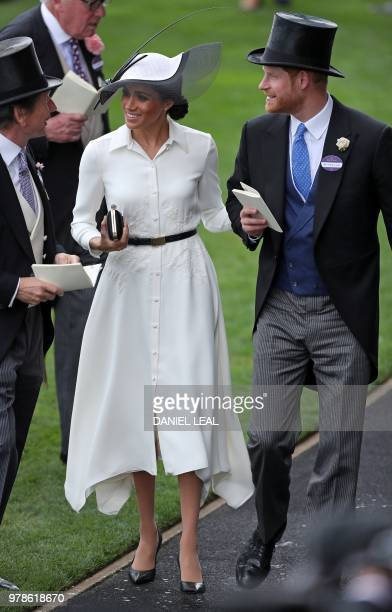 Britain's Prince Harry Duke of Sussex and his wife Britain's Meghan Duchess of Sussex talk with the Queen's Bloodstock and Racing Advisor John Warren...