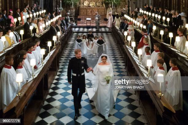 TOPSHOT Britain's Prince Harry Duke of Sussex and his wife Britain's Meghan Markle Duchess of Sussex leave St George's Chapel after their wedding...