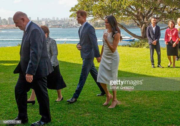 Britain's Prince Harry Duke of Sussex and his wife Meghan Duchess of Sussex walk to a photo opportunity with the Australian GovernorGeneral Sir Peter...