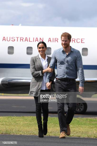 Britain's Prince Harry Duke of Sussex and his wife Meghan Duchess of Sussex arrive at Dubbo Regional Airport in Dubbo on October 17 2018 The rain was...