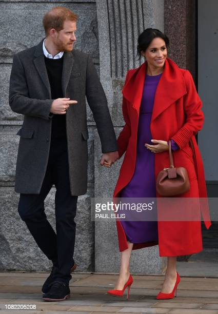 Britain's Prince Harry Duke of Sussex and his wife Meghan Duchess of Sussex react during their visit to Birkenhead northwest England on January 14...