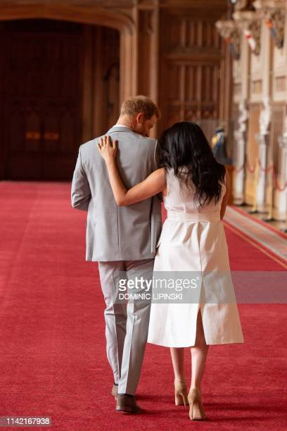TOPSHOT Britain's Prince Harry Duke of Sussex and his wife Meghan Duchess of Sussex walk away after posing for photographs with their newborn baby...