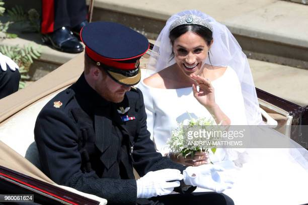 Britain's Prince Harry Duke of Sussex and his wife Meghan Duchess of Sussex wave from the Ascot Landau Carriage after their wedding ceremony at St...
