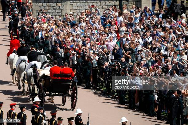 Britain's Prince Harry Duke of Sussex and his wife Meghan Duchess of Sussex begin their carriage procession in the Ascot Landau Carriage after their...