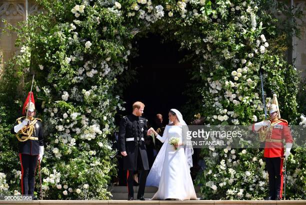 TOPSHOT Britain's Prince Harry Duke of Sussex and his wife Meghan Duchess of Sussex emerge from the West Door of St George's Chapel Windsor Castle in...